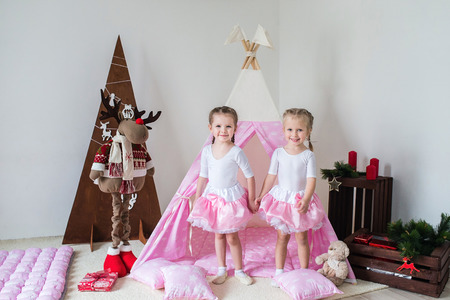 Two little girls, sisters, friends play in a tent in a house or teepee.