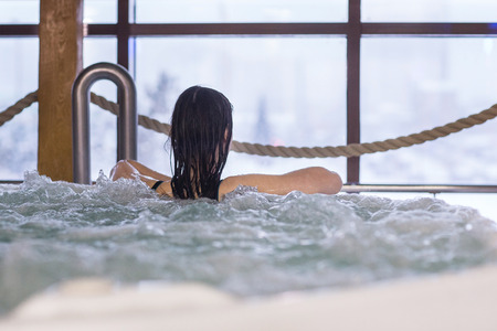 water hottub: Beautiful spa. Back view of a young woman enjoying in a spa center Stock Photo