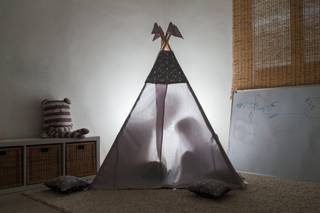 Adult and child sitting in a teepee in the nursery.