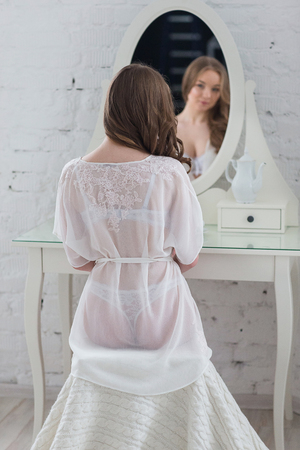 Gentle woman in white lingerie sits behind the night table