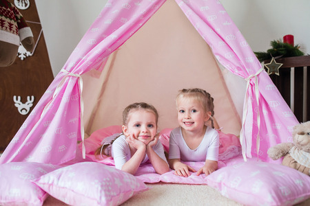 Two little girls play in a teepee Stock Photo