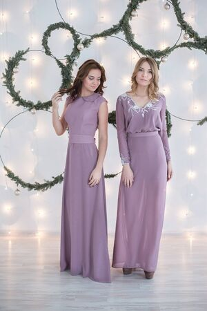 artificial lights: Two woman in dress in front of wall decorated