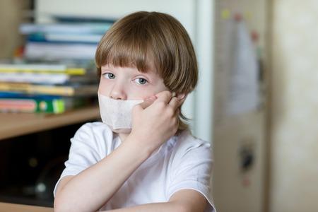 pegamento: niño se sienta con la boca sellada de cinta Foto de archivo