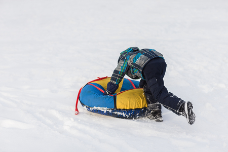 affable: Happy child pushes the tubing in the snow in the winter frosty day Stock Photo