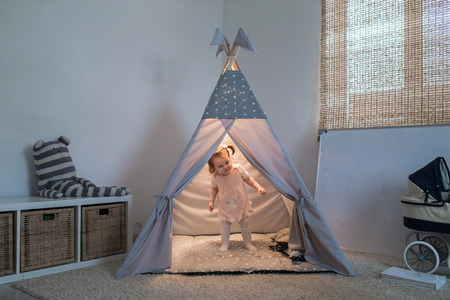 Girl playing in the teepee