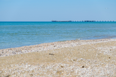 reprimanding: Pier in the black sea in the distance on the background of blue clear Sunny sky