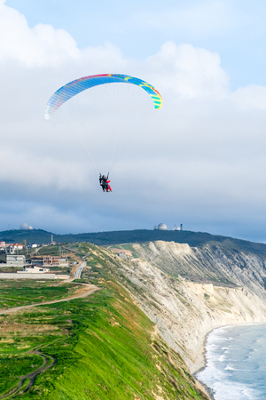 Flying tandem paragliders over the sea close to mountains, vertical view of the landscape