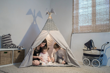 mother reads book in a teepee Stock Photo