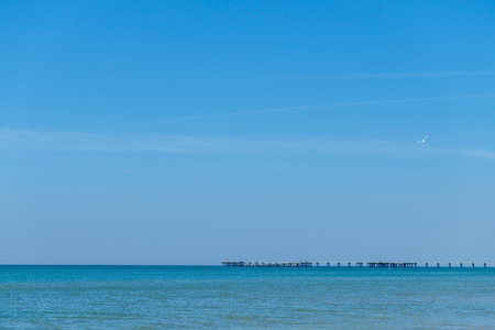 Pier in the black sea in the distance on the background of blue clear Sunny sky