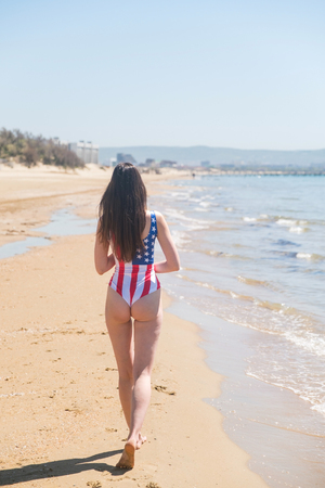 Rear view of beautiful young woman patriot USA on the ocean
