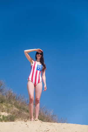Beautiful young patriot USA on blue sky background in a swimsuit