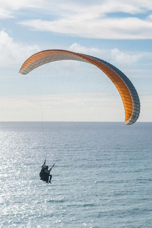 Flying tandem paraglider over the sea, vertical shot