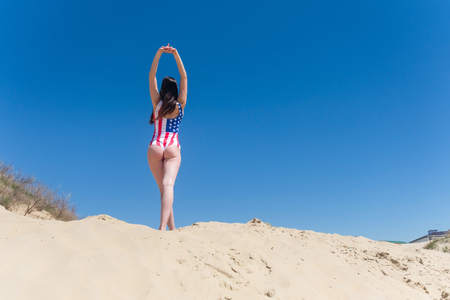 Beautiful young patriot USA back to camera on blue sky background in a swimsuit