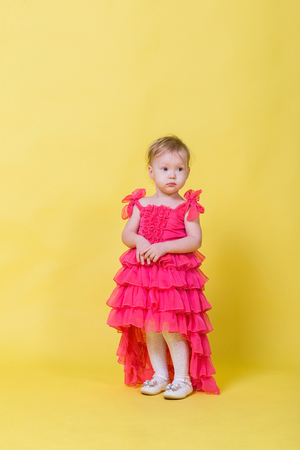 Girl toddler in a pink dress on a yellow background in the Studio