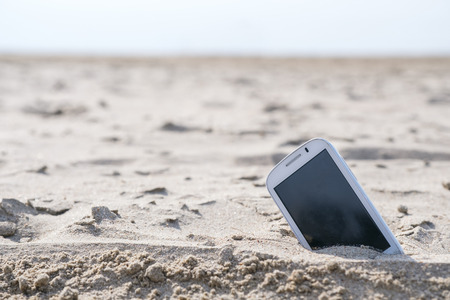 Mobile touch phone in sand on a beach