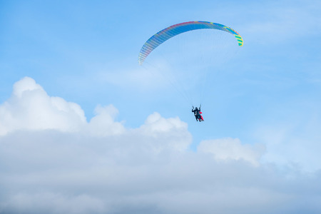 free education: Paragliders in bright blue sky, tandem of instructor and beginner