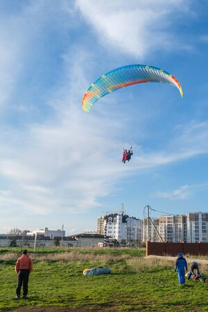 Landing a tandem paraglider on paradrome on a Sunny day. Stock Photo