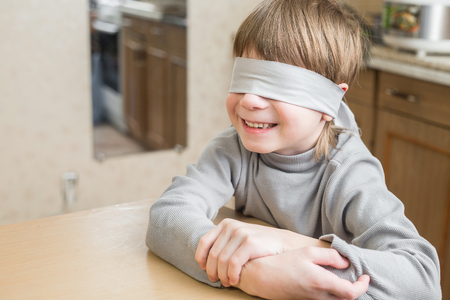 The child was blindfolded at home