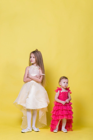 argue kid: Two sisters in dresses on a yellow background look in different directions and offended Stock Photo