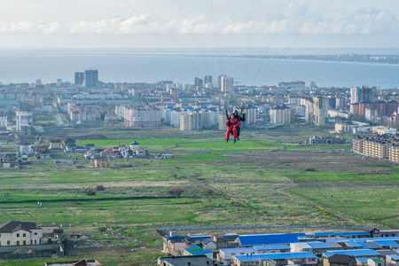 Flying tandem paragliders over the city on a Sunny day Stock Photo