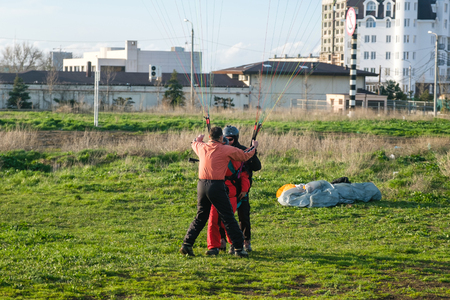 Landing a tandem paraglider on paradrome on a Sunny day