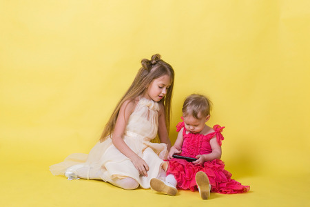 Two sisters in dresses on a yellow background and a mobile smartphone