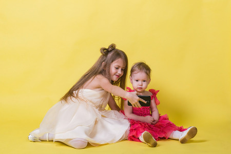 Two sisters in dresses on a yellow background photographed themselves on the phone