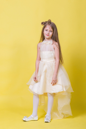Teenager girl in a dress on a yellow background poses for the camera