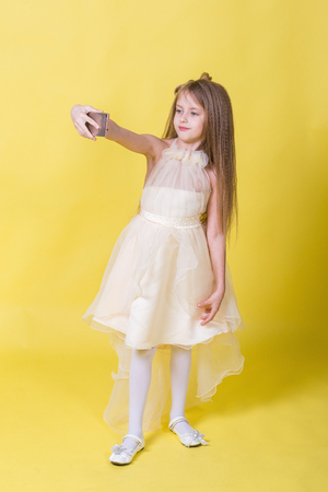 Teenager girl in a dress on a yellow background photographed themselves on the phone Stock Photo