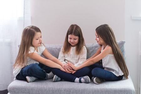 couch: Portrait of three happy girls sitting on sofa and friendship concept Stock Photo
