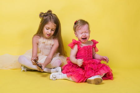 The younger sister cries, the elder keeps the phone on yellow background