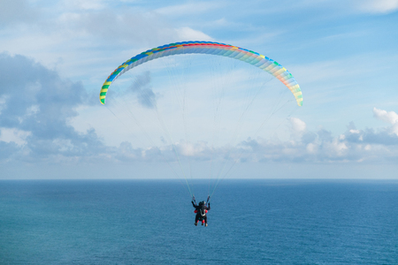 Flying a tandem paraglider over the sea with views of the horizon Stock Photo