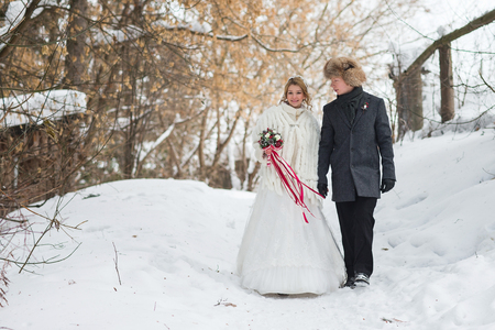 Young couple newlyweds walking in a winter forest in the snow. Stock Photo