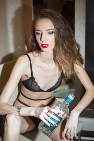 Brunettefrau in der Wäsche in der Küche mit einer Flasche Alkohol in der Hand Standard-Bild