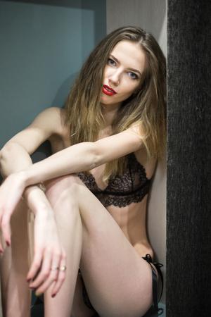 prostituta: Morena joven mujer se sienta en un armario en el dormitorio en el país Foto de archivo