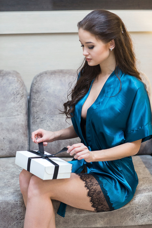 Young beautiful woman in lingerie with gift in hand on sofa Stock Photo