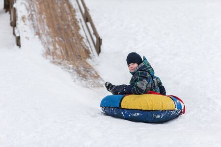 happy child is heading to ice mountain for tubing in the winter Stock Photo