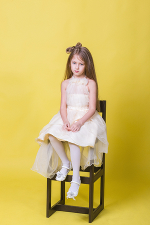 Teenager girl in a dress on a yellow background posing for the camera and sits on the chair Stock Photo