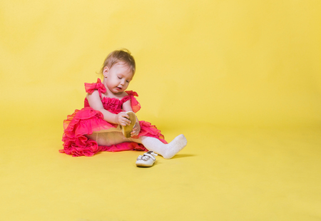 Girl toddler in a pink dress on a yellow background wearing the shoes on his feet