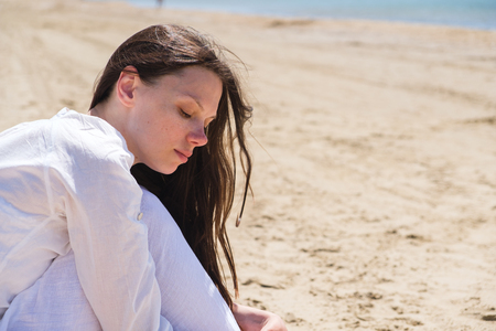Young woman looking away while sitting at sea shore Stock Photo