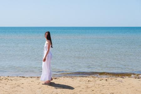 Woman in white dress near the sea in half-turn on the sea.