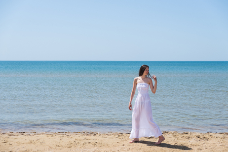 A woman in a white dress walks on the beach