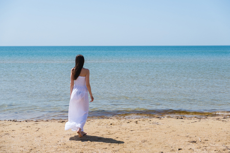 Young brunette woman in summer white dress standing on beach and looking to the sea.