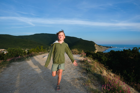 Six year old boy running on a mountain road at sunset with town and sea view. Cool summer evening.