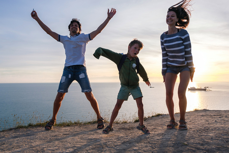 Family fun pastime on a mountain with seaside view. Dad, mom, and son dance at sunset. Front view.