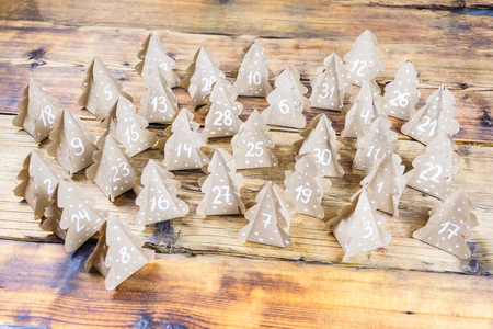 Handmade Christmas advent calendar Christmas trees Kraft paper with numbers in wood background.