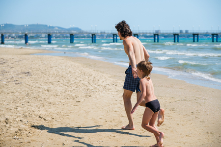Dad and his son run along the beach to the pier in swimming trunks. Beach holiday.
