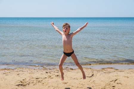 Six-year-old boy in black speedo jumping into the sea and shouts. Stock Photo