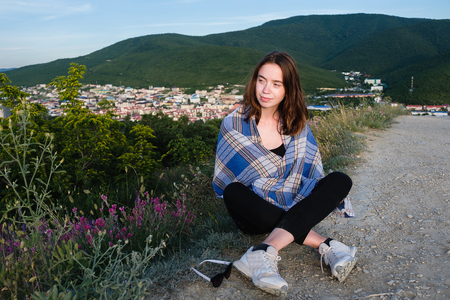 Young girl sits on a mountain, wrapped in a blanket. Cool summer evening in the mountains.