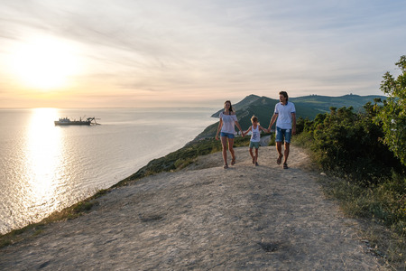 Family mom, dad and son walking down a mountain road with seascape at sunset. Front view. Banco de Imagens